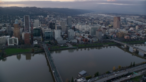 AX155_153.0000126F - Aerial stock photo of Downtown Portland skyscrapers and city park seen across the Willamette River at sunset