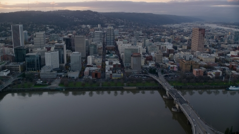 AX155_153.0000340F - Aerial stock photo of Downtown Portland skyscrapers and city park seen across the Willamette River at sunset