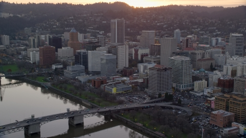 AX155_155.0000000F - Aerial stock photo of Downtown Portland skyscrapers and city park beside the Willamette River at sunset