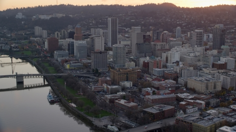 AX155_155.0000261F - Aerial stock photo of Downtown Portland skyscrapers and city park beside the Willamette River at sunset