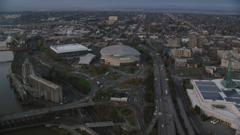 AX155_175.0000153F - Aerial stock photo of I-5 near Veterans Memorial Colosseum and Moda Center in Lloyd District, Portland, Oregon, sunset