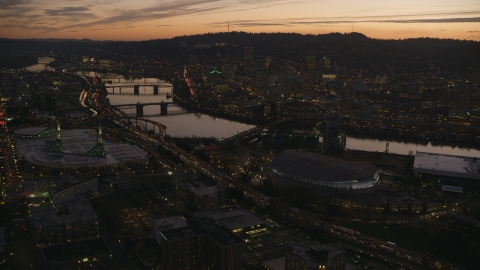 AX155_260.0000149F - Aerial stock photo of Moda Center, Willamette River, and downtown skyscrapers at sunset, Downtown Portland, Oregon