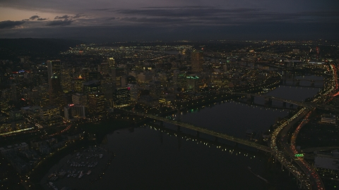 AX155_268.0000248F - Aerial stock photo of Downtown Portland's cityscape beside the Willamette River at sunset, Oregon