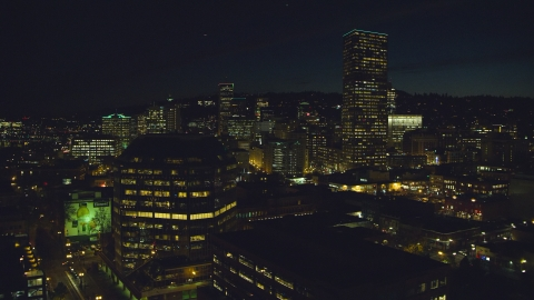 AX155_368.0000040F - Aerial stock photo of One Pacific Square, with US Bancorp Tower and high-rises in the background at night, Downtown Portland, Oregon