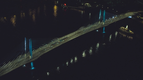 AX155_416.0000264F - Aerial stock photo of Tilikum Crossing bridge as a commuter train crosses the span at night in South Portland, Oregon
