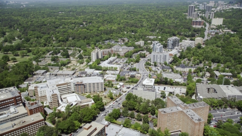 AX36_048.0000176F - Aerial stock photo of Peachtree Road near hospital, skyscrapers and wooded area in distance, Buckhead, Georgia