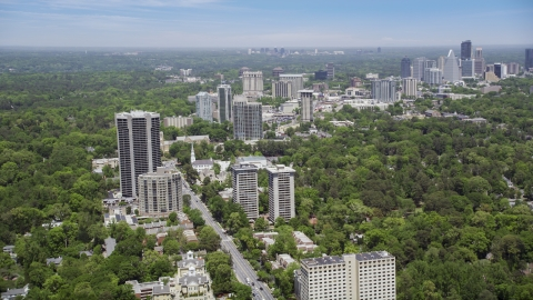 AX36_050.0000144F - Aerial stock photo of Peachtree Road past office buildings and wooded area, Atlanta, Georgia