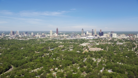 AX37_006.0000258F - Aerial stock photo of Midtown and Downtown Atlanta seen from above the trees in West Atlanta, Georgia