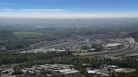 AX37_085.0000025F - Aerial stock photo of Train yard surrounded by green trees, Atlanta, Georgia