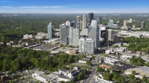 AX38_012.0000306F - Aerial stock photo of Skyscrapers overlooking forests, Buckhead, Georgia