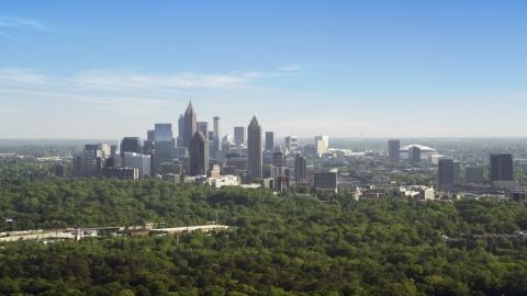 AX38_028.0000097F - Aerial stock photo of Midtown Atlanta skyscrapers beyond trees, Buckhead, Georgia