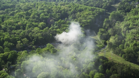 AX38_036.0000127F - Aerial stock photo of Smoke from a burning home in a wooded area, West Atlanta, Georgia