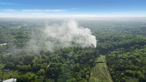 AX38_048.0000129F - Aerial stock photo of Smoke rising from a house fire in a wooded area, West Atlanta, Georgia
