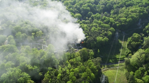 AX38_049.0000254F - Aerial stock photo of Smoke rising from a burning house in a wooded area, West Atlanta, Georgia