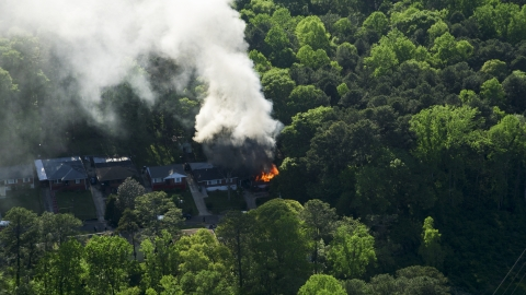 AX38_052.0000129F - Aerial stock photo of Smoke and flames rising from a burning home, West Atlanta, Georgia