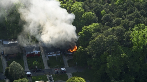 AX38_052.0000382F - Aerial stock photo of Smoke and flames from a burning home, West Atlanta, Georgia