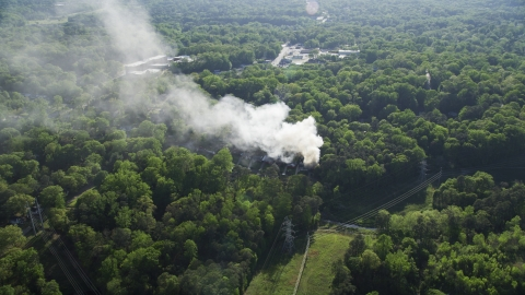 AX38_054.0000181F - Aerial stock photo of Smoke rising from a burning house in a wooded area, West Atlanta, Georgia