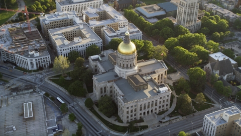 AX39_040.0000072F - Aerial stock photo of Georgia State Capitol and its gold dome, Downtown Atlanta, sunset