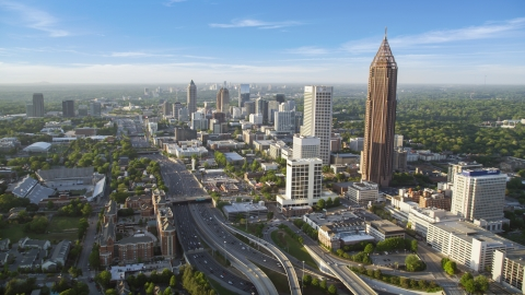 AX39_049.0000050F - Aerial stock photo of Downtown Connector along city buildings; Midtown Atlanta, Georgia, sunset