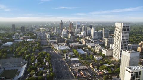 AX39_049.0000319F - Aerial stock photo of Downtown Connector along city buildings; Midtown Atlanta, Georgia