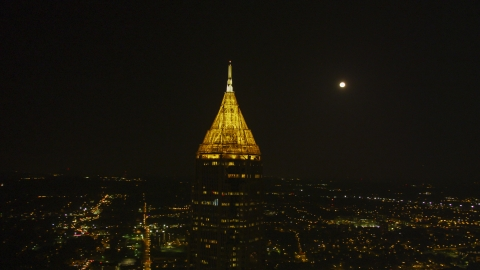 AX41_026.0000212F - Aerial stock photo of The top of Bank of America Plaza at night with moon in the background, Midtown Atlanta, Georgia
