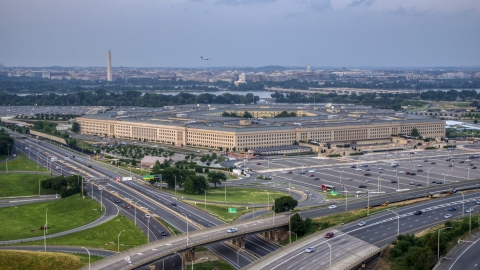 AXP076_000_0024F - Aerial stock photo of The Pentagon at twilight in Washington, D.C., with the Washington Monument in the distance