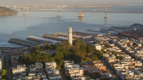 DCSF07_008.0000069 - Aerial stock photo of Coit Tower with Bay Bridge in background, North Beach, San Francisco, California, sunset