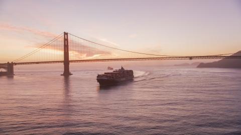 DCSF10_041.0000043 - Aerial stock photo of A cargo ship sailing by the Golden Gate Bridge, San Francisco, California, twilight