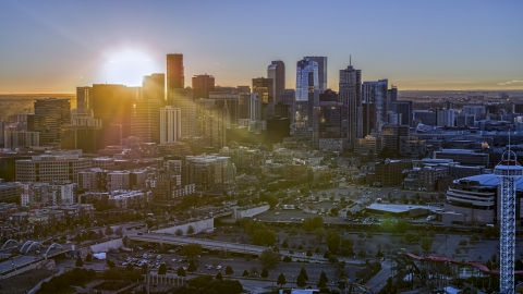 DXP001_000094 - Aerial stock photo of Sun rising behind the city's skyline in Downtown Denver, Colorado