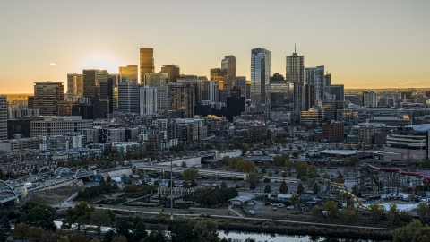 DXP001_000097 - Aerial stock photo of Bright sun rising behind the city's skyline in Downtown Denver, Colorado