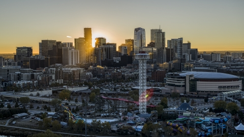 DXP001_000098 - Aerial stock photo of Bright sun rising behind the city's skyline, Elitch Gardens and Pepsi Center arena in Downtown Denver, Colorado