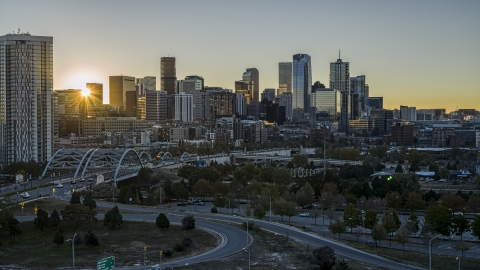 DXP001_000099 - Aerial stock photo of The city skyline with the bright sun rising behind the skyscrapers in Downtown Denver, Colorado