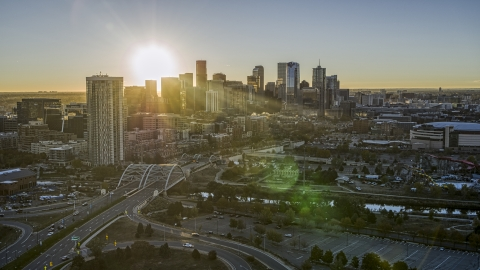DXP001_000101 - Aerial stock photo of The city skyline with the bright sun above the skyscrapers at sunrise in Downtown Denver, Colorado