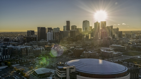 DXP001_000107 - Aerial stock photo of The sun shining above the skyscrapers of the city's skyline at sunrise, seen from arena in Downtown Denver, Colorado