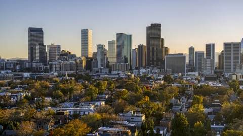 DXP001_000180 - Aerial stock photo of City's skyline seen from tree-lined residential neighborhood at sunset, Downtown Denver, Colorado