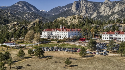 DXP001_000208 - Aerial stock photo of The historic Stanley Hotel with mountains behind it in Estes Park, Colorado