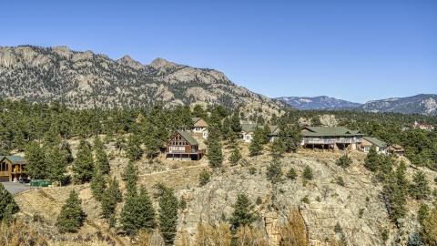 DXP001_000229 - Aerial stock photo of Rural hillside homes near rugged mountains, Estes Park, Colorado