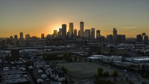 DXP001_000258 - Aerial stock photo of The bright sun behind tall skyscrapers in the city's skyline at sunrise in Downtown Minneapolis, Minnesota