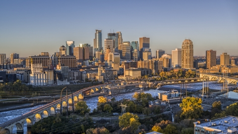 DXP001_000354 - Aerial stock photo of The downtown skyline seen from the Stone Arch Bridge spanning the river at sunrise, Downtown Minneapolis, Minnesota