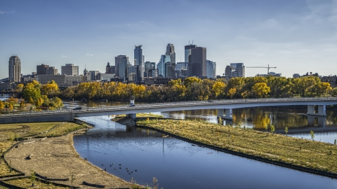DXP001_000398 - Aerial stock photo of City skyline's skyscrapers seen from a bridge crossing the Mississippi River with fall trees, Downtown Minneapolis, Minnesota