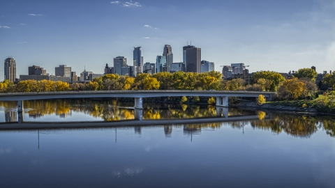 DXP001_000401 - Aerial stock photo of A view of the city skyline from near a bridge over the Mississippi River with fall trees, Downtown Minneapolis, Minnesota