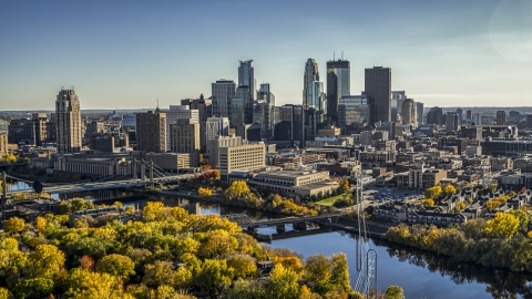 DXP001_000411 - Aerial stock photo of Bridges spanning the river near autumn trees, and the skyline in the background, Downtown Minneapolis, Minnesota