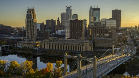 DXP001_000415 - Aerial stock photo of Skyline seen from the Hennepin Avenue Bridge crossing the river at sunset, Downtown Minneapolis, Minnesota