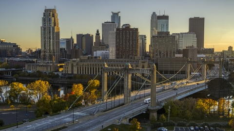 DXP001_000416 - Aerial stock photo of Hennepin Avenue Bridge spanning the river at sunset, skyline in the background, Downtown Minneapolis, Minnesota