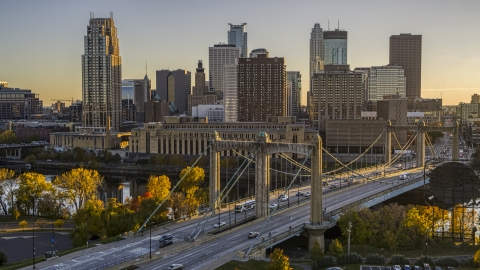 DXP001_000417 - Aerial stock photo of Traffic crossing the Hennepin Avenue Bridge spanning the river at sunset, skyline in the background, Downtown Minneapolis, Minnesota
