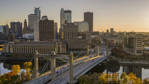 DXP001_000418 - Aerial stock photo of Cars crossing the Hennepin Avenue Bridge spanning the river at sunset, skyline in the distance, Downtown Minneapolis, Minnesota