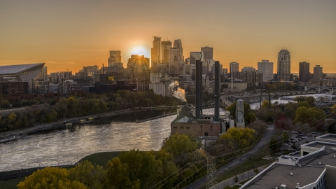 DXP001_000422 - Aerial stock photo of The setting sun behind the skyline across the river, seen from a power plant, Downtown Minneapolis, Minnesota