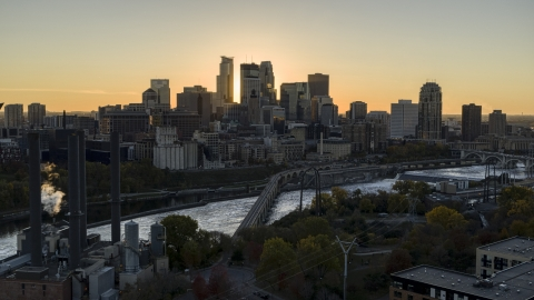 DXP001_000423 - Aerial stock photo of The sun setting behind the skyline across the Mississippi River, Downtown Minneapolis, Minnesota