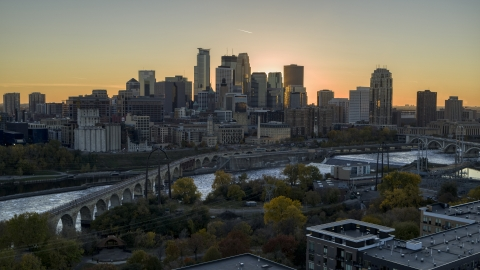 DXP001_000427 - Aerial stock photo of The city skyline across the river at sunset, seen from the Stone Arch Bridge, Downtown Minneapolis, Minnesota