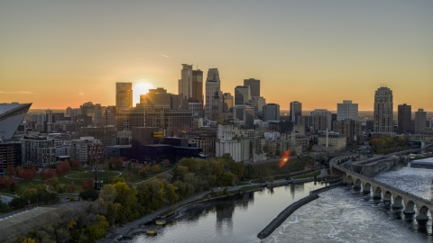DXP001_000428 - Aerial stock photo of The city skyline on the other side of the river at sunset, seen from near a bridge, Downtown Minneapolis, Minnesota